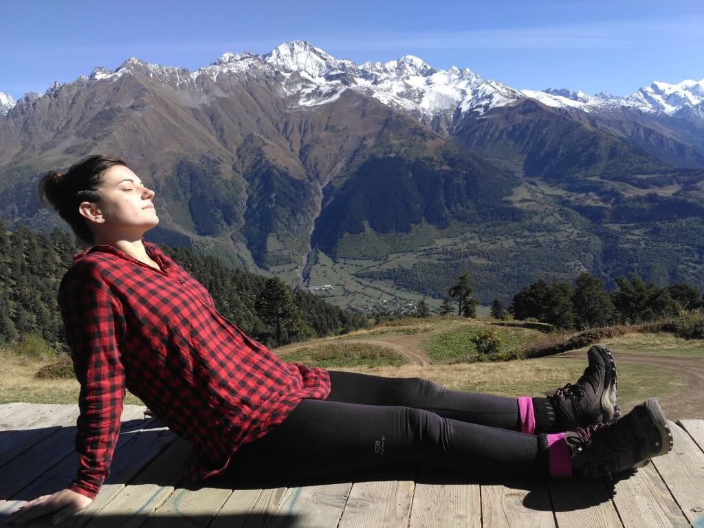 Girl relaxes in the sun in front of mountain