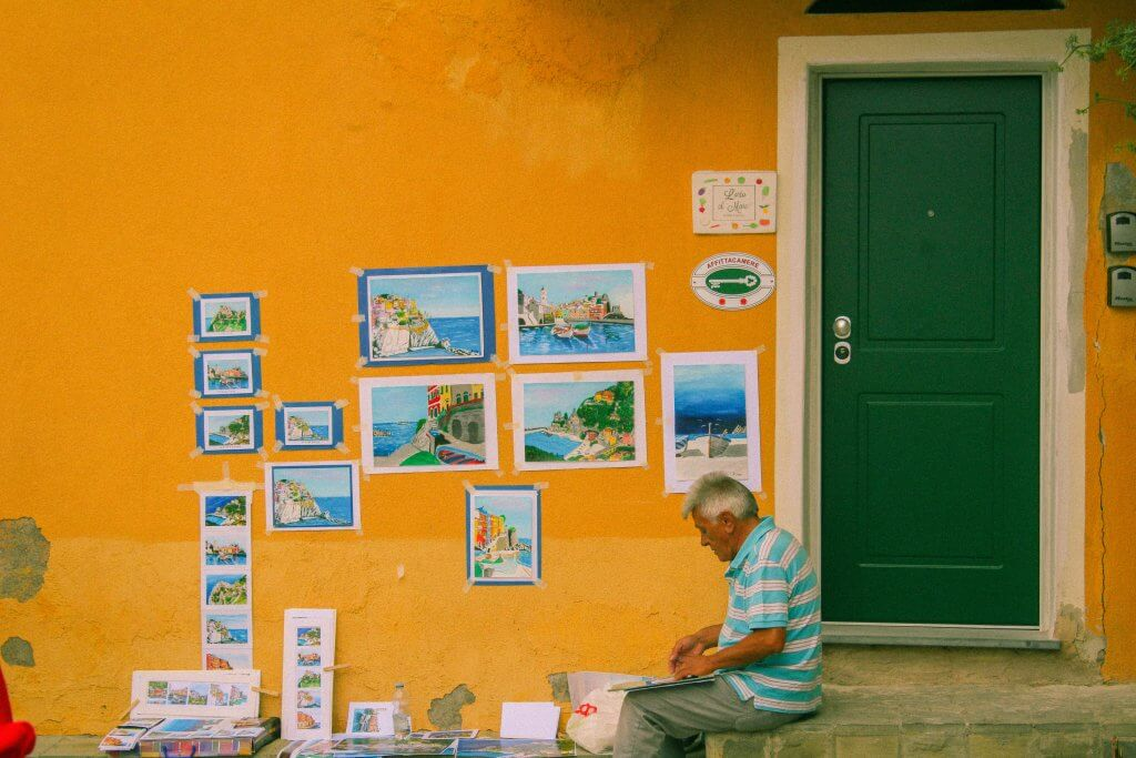 man paints in front of yellow wall