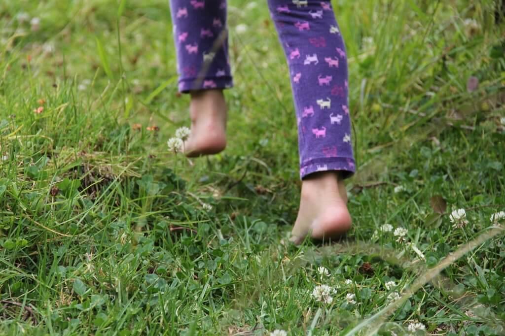little girl walking in the grass