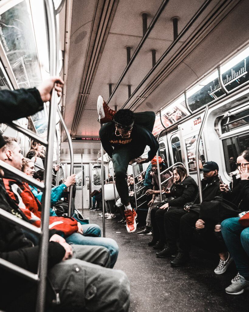 man breakdances in a metro